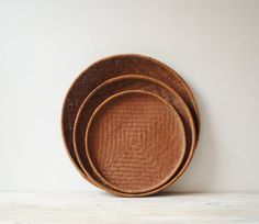 """Set of three vintage bamboo basket trays in excellent vintage condition. Beautiful old pieces with nice patina to them. No holes. Great as decor on your shelf or for wrangling items on a coffee table. All three have a diamond pattern woven into the bottom.   Large tray: 18"""" diameter x 1"""" thick Medium tray: 15.5"""" diameter x 1"""" thick. Small tray: 13"""" diameter x 1"""" thick"""