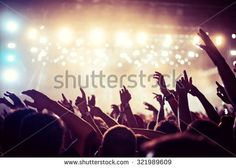 Audience with hands raised at a music festival and lights streaming down from…