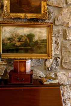 I love the beautifully framed art against the rough stone walls.