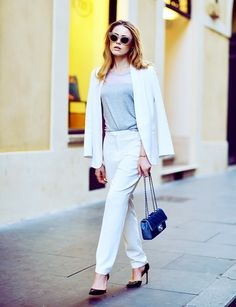 A white suit is paired with a gray T-shirt, a blue bag, and black heels