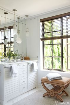 Louvered cabinets in this bathroom add visual texture via @Veranda Magazine #white #modern