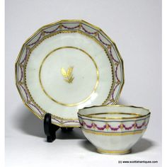 New Hall Fluted Porcelain Tea Bowl & Saucer c1790Marks : Unmarked Origin : English Colour : Puce and gilt Pattern : Pattern 94 Features : Fluted form. A Band of magenta swags and gilt pendants set between black lines and a dentil border.