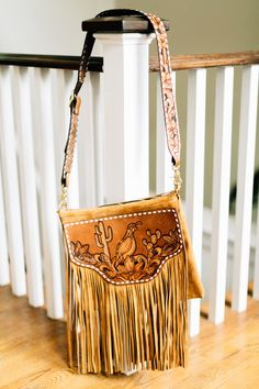 "A modern bag with a retro twist, this bag has it all! The body of this bag is made from a toast suede leather with fringe for days! it features a lined interior with one pocket, zipper closure, brass hardware and a fully tooled adjustable strap. Length: 12"" Width: 14"""