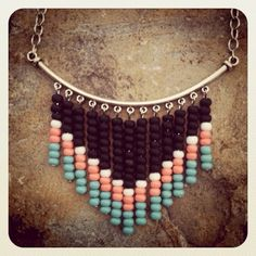 "Handmade Native American-inspired bib style necklace featuring rows of colorful turquoise, coral pink/orange, white, and matte black seed beads arranged in a chevron/arrow pattern along a silver plated arc. Silver arc bar is 3"" long, beads dangle down 2"" at the longest length. Silver plated ch..."