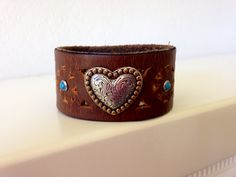 Narrow repurposed leather band with cutouts. Perfect for this gold and silver heart!