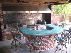 Outdoor kitchen in the Sugar Land, Texas area with large vent hood, concrete counters, Big Green Egg, Grill, range and more. It is the Total backyard outdoor living area.
