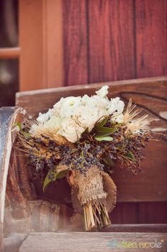 Country style bouquet of cream blooms with wheat and berry accents wrapped with burlap. By Layers of Lovely Floral Design