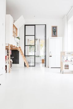 modern whitewashed kids playroom with black steel framed glass windows and door. Diy Crafts On A Budget, White Beams, Dark Interiors, Interior Decorating, Interior Design, Küchen Design, Modern Design, Color Stories, Concrete Floors