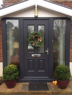 This dark front door framed by stained glass is an elegant way to open up your home by expanding on the windows. The dark door accents the brick house and plants add a necessary touch of green. Grey Front Doors, Front Door Porch, Porch Doors, Front Porch Design, Double Front Doors, House Front Door, House With Porch, Entry Doors, Porch Entrance