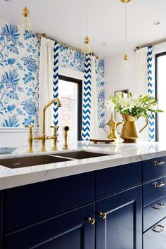 As seen on season one of Sarah Sees Potential, designer Sarah Richardson filled this century-old kitchen with a mix of modern amenities and vintage charm. The large eat-in kitchen island was topped with a premium slab of Calacatta marble and painted a rich blue to match the room's traditional blue and white floral wallpaper. Brass pendant lights hang over the stainless steel sink and complement the room's brass hardware, completing the cohesive design.