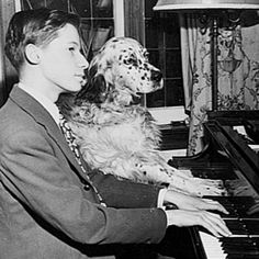 A young Glenn Gould and a sweet dog playing the piano.