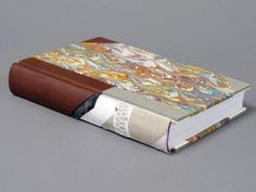 """""""Library style"""" split board binding by Whitney Baker; British; 19th century. Morocco spine & corners with marbled paper sides; sewn with a link stitch on linen tapes; red & blue silk sewn endbands on linen cord core; made ends of plain & marbled paper; linings of kizukishi, airplane linen, Permalife, & leather (sanded); split boards constructed from binder's board and 4-ply matboard; when opened, cutaway allows viewer to see the flange sandwiched between the split boards. 24 x 16 x 4 cm."""