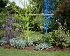 Paint dead trees a bright color for instant garden art! Why didn't I think of this?