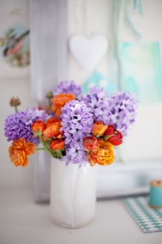 Lilac and burnt orange flowers in white ceramic vase