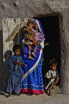 Mother with children out side her village house | Sindh Pakistan.