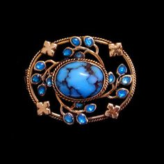JESSIE M. KING (1875-1949) LIBERTY & Co.  A gold brooch, set with a central turquoise, surrounded by enamelled buds  and gold leaves.