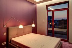 Przytulna aranżacja sypialni w kolorze fioletowym z tapicerowanym zagłówkiem nad łóżkiem i praktycznymi lampkami nocnymi.