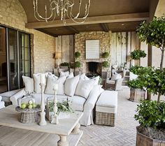 Amazing patio with Aidan Gray Graceful Elegance Candle Chandelier, outdoor stone fireplace, wicker chairs, brick pavement in herringbone pattern, rolled-arm slipcover sofa with pillows and reclaimed wood coffee table.