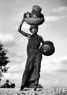 Margaret Bourke-White - Stately woman carrying grain pots in basket on her head & in her hand as she goes to get meager food supplies due to famine caused by drought. India, 1946. S)