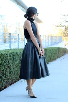 Love this look. Studded t-strap stilettos, A line skirt, sleeveless turtleneck, clean bun. So chic!