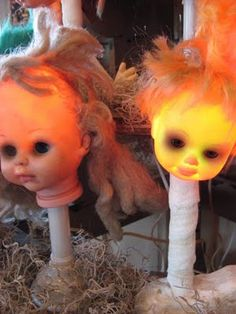 Doll Heads = Creepy dolls!  Looks like they might be on a flashlight that is wrapped in white tissue.