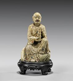 """CARVED SOAPSTONE LOHAN 皂石雕持塔羅漢坐像 Chinese carved soapstone figure; of a disgruntled-looking Lohan, holding a pagoda in his hands, wearing finely incised robes inset with some glass cabochons, and seated upon rockery; H: 5 3/8"""", wood stand"""