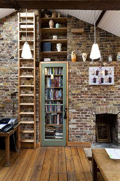 exposed brick wall with book shelves and a fireplace, living room