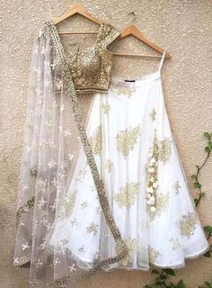 Gold mirror work blouse with tassels, teamed with white net lehenga with raw silk underlay and Pearl Butis, and net dupatta with white threadwork butis and mirror border workrlay. Handwork on lehenga and dupattaCan be colour customisedAll prod. Indian Lehenga, Lehenga Choli, Net Lehenga, Gold Lehenga, Lehenga Blouse, Lehenga White, Indian Saris, Indian Attire, Indian Wear