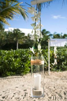 White orchids and hanging pillar candles are a beautiful choice for a seaside #wedding celebration.