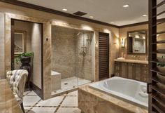 This large, luxurious bathroom is awash in marble, surrounding the jacuzzi tub and wrapping the large walk-in shower. Discrete vanities face across the expansive tile floor.