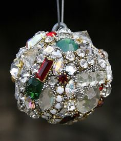 An assortment of vintage rhinestones have been meticulously set upon a sphere making for a beautiful one-of-a-kind treasure for your Christmas tree. These little glittery orbs look fabulous when grouped or tucked into a found nest or treasured cup. I feather our nest year-round with a gathering of bottles and jeweled ornamental orbs. The look never ceases to gain appreciative attention! This little ball is all jeweled up in the holidays traditional colors!  Measures just over a 1 3/8  I ...