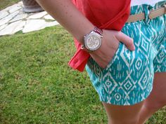 Turquoise printed shorts, blinged out watch and a pop of red
