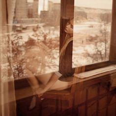 Девушка сидит у окна, за которым видна городская улица с домами, работа одиночество, фотограф Сергей Филимонов
