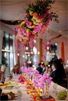 Beautiful orchid centerpieces with candles and hanging flower arrangements ~ Photo: MiaBella Photography