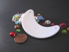 These high-fire porcelain pendant blanks can be used in so many ways! They can be apllied with beads, buttons, cabochons, cameos, rhinestones - you name it. They can also be glazed and kiln-fired, painted with acrylic or enamels, or even decoupaged!  Great for teachers, craft projects, or your own business.   2.75 from side to side and 1.25 at the widest area.  Sold in sets of twelve, but will offer incentives and combine shipping for larger orders.