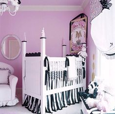 This nursery is girly and bold with a pink, black, and white color palette. The pink walls and ruffled window treatments show that this room is meant for a baby.