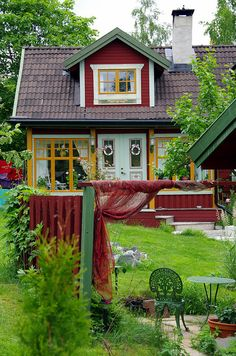 Pretty little cottage in the garden. love the red with mustard yellow trim