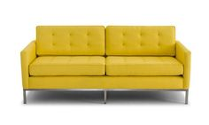 The minimalist style brings out the loveseat's classic lines, highlighting its unique metal base and retro design elements.