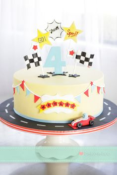 Vroom vroom car racing themed cake. I like the circle track on the cake stand around the cake.