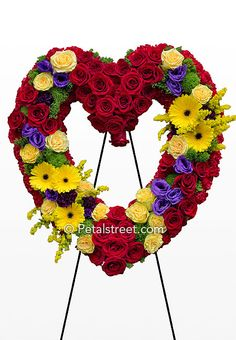 Heart shaped funeral wreath with red roses and bright yellow Gerbera Daisies by Petal Street Flower Company.