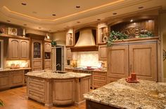 Large luxury kitchen with two kitchen islands, tray ceiling and wood floor