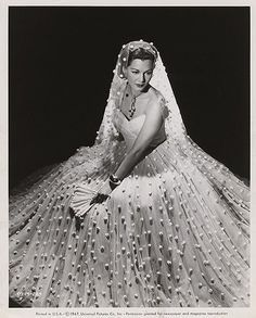 """Maria Montez (1912 – 1951) was a  motion picture actress who gained fame and popularity in the 1940's as an exotic beauty starring in a series of filmed-in-Technicolor costume adventure films. Her screen image was that of a Latin seductress, dressed in fanciful costumes and sparkling jewels. She was so identified with these adventure epics that she became known as """"The Queen of Technicolor."""""""