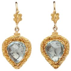 Victorian Heart to Heart Aquamarine Gold Earrings. The beautiful blue aquamarines in these Victorian earrings glow like sunshine on the water. The pear cut aquas are set in a heart shaped frame covered with embossed gold vines. English origin circa 1840.