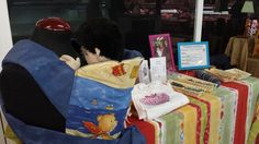 En la feria de artesanía del Mercado de Vallehermoso encontrarás Mei Tai, un portabebé de origen asiático. Consta de un rectángulo de tela y cuatro tiras que se anudan a la cintura y a la espalda del portador, a partir de 6 meses.