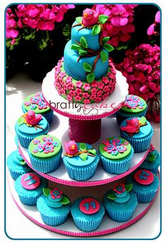 I'm not usually a huge fan of cupcake towers, but this one is adorable with the mini cake on top.  Image via the Cupcake Blog, from May 25, 2011.