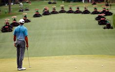 Tiger Woods of the United States stands on the green as grounds crew mow the the fairways during a practice round prior to the start of the 2015 Masters Tournament at Augusta National Golf Club in Augusta, Georgia