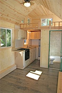 """House Tour: Inside This 150 Square Foot House By Molecule Tiny Homes - This house is only 8' 6"""" wide by 20' long by 13' 5"""" high. Inside, it has two sleeping lofts, a full kitchen including a three-burner range and oven and a full bathroom with shower and tub."""