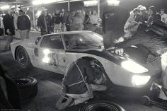 Pit crewman replace the tires and top up fluids on a Ford GT40 endurance racer at the 1966 24 hours of Daytona