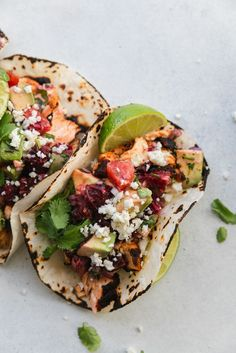 These Blackened Salmon Tacos are topped with the most delicious and fresh blood orange avocado salsa. They come together in 20 minutes or less, and you only need 9 ingredients! They're topped with crumbled queso fresco cheese and extra cilantro and lime too! #20minutemeal #bloodorange #tacos #salmon #easymeal #glutenfree