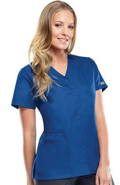 This short-sleeve, snap front tunic scrub top from Cherokee Workwear Originals has two patch pockets, one cell phone pocket, and side vents. Made of soil-release poly/cotton poplin. Missy traditi...